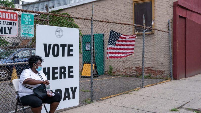 Un trabajador electoral se sienta fuera del colegio electoral en Saint Aloysius en Jersey City, N.J. el 7 de julio de 2020. (David Dee Delgado/Getty Images)