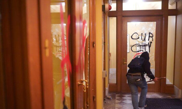 Un agitador corre por el vandalizado vestíbulo del ayuntamiento de Portland, Oregón, la noche del 25 de agosto de 2020. (Nathan Howard/Getty Images)