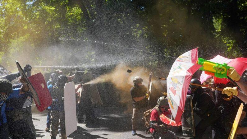 Los manifestantes a favor de la policía y otros (izq.) y contramanifestantes, disparan gas pimienta y se arrojan objetos frente al Centro de Justicia del Condado de Multnomah en Portland, Oregón, el 22 de agosto de 2020. (Nathan Howard/Getty Images)