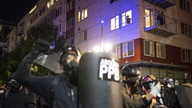 Oficiales de policía de Portland dispersan a los alborotadores junto al fuego de un contenedor cerca del centro de detención del Servicio de Control de Inmigración y Aduanas de Portland, Ore, a principios del 21 de agosto de 2020.  (Nathan Howard/Getty Images)