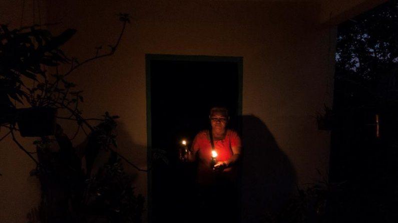 Fotografía de archivo fechada el 03 de marzo del 2020 donde se observa a una mujer iluminar fuera de su casa durante un apagón en la ciudad de Maracaibo (Venezuela). EFE/ Henry Chirinos /Archivo