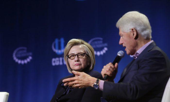La exsecretaria de Estado, Hillary Clinton, escucha mientras el expresidente, Bill Clinton, habla durante la conferencia anual de la Iniciativa Global Clinton en la Universidad de Chicago en Chicago, Illinois, el 16 de octubre de 2018. (Joshua Lott/Getty Images)