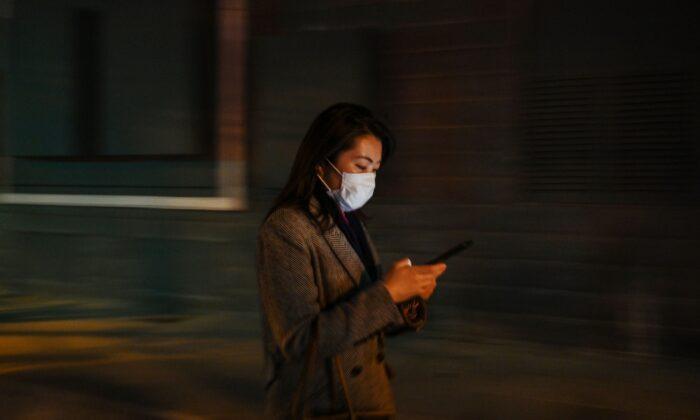 Una mujer revisa su teléfono celular en Shanghai, China, el 17 de marzo de 2020. (HECTOR RETAMAL/AFP vía Getty Images)