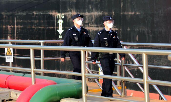 Los agentes de policía con mascarillas ven un buque petrolero que descarga petróleo crudo en el puerto de Qingdao, provincia de Shandong, al este de China, el 20 de marzo de 2020. (STR/AFP a través de Getty Images)