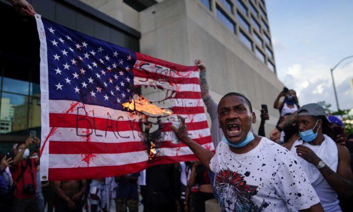 Los manifestantes queman una bandera frente al CNN Center, en Atlanta, Georgia, el 29 de mayo de 2020. (Elijah Nouvelage/Getty Images).
