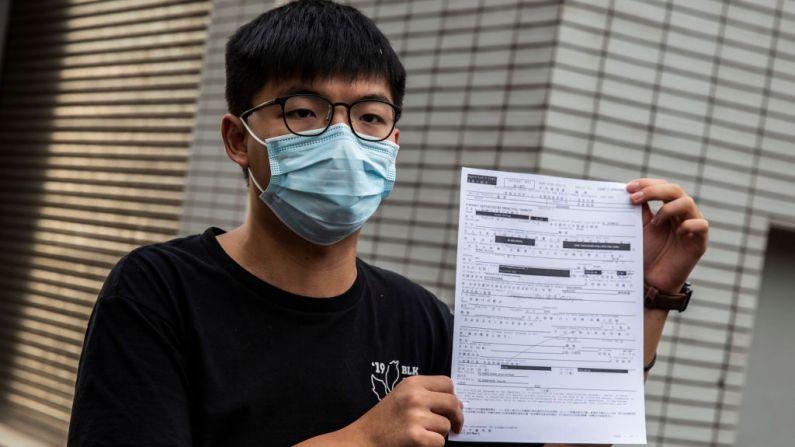 El activista prodemocracia de Hong Kong, Joshua Wong, habla con los medios de comunicación mientras sostiene un documento de fianza después de salir de la estación central de policía de Hong Kong el 24 de septiembre de 2020. Fue arrestado por una reunión ilegal relacionada con una protesta en 2019, contra ley antimáscara del gobierno. (LAWRENCE/AFP vía Getty Images)