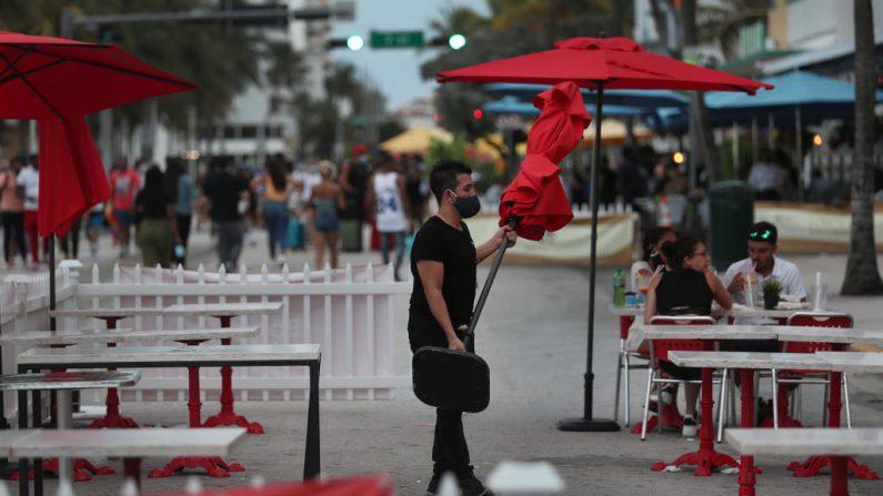 Un trabajador de un restaurante quita una sombrilla de la zona de asientos exteriores y se prepara para cerrar el restaurante por el día en Miami Beach, Florida (EE.UU.) el 18 de julio de 2020. (Foto de Joe Raedle/Getty Images)