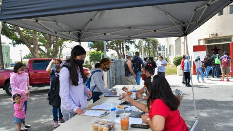 El subdirector Samuel Dovlatian y Karla Rosales registran a los estudiantes de la Escuela Secundaria de Hollywood el 13 de agosto de 2020 en Hollywood, California (EE.UU.). (Foto de Rodin Eckenroth/Getty Images)