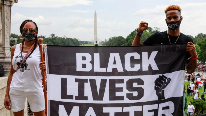 Los manifestantes sostienen un cartel en apoyo de Black Lives Matter durante la Marcha del Compromiso en Washington, DC el 28 de agosto de 2020. (Natasha Moustache/Getty Images)