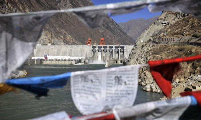 Esta fotografía tomada el 23 de noviembre de 2014 muestra banderas de oración colgadas frente a la central hidroeléctrica de Zangmu en el condado de Gyaca en Lhoka, o prefectura de Shannan, región del Tíbet al suroeste de China. (STR/AFP a través de Getty Images)