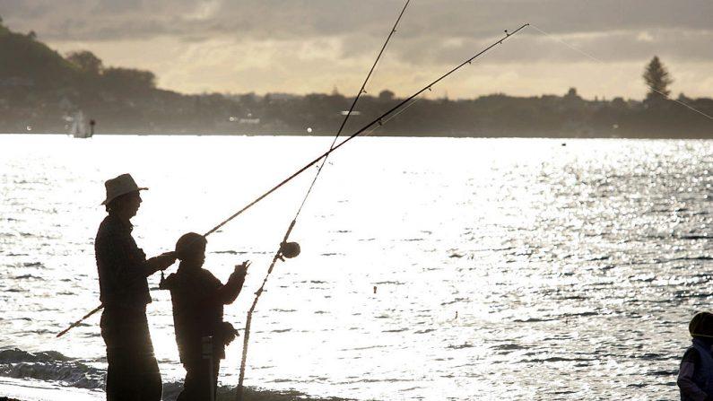 Un padre y un hijo disfrutan del sol de la tarde y un lugar de pesca en Mission Bay en Auckland, Nueva Zelanda, el domingo 19 de junio de 2005 (Sandra Mu / Getty Images)