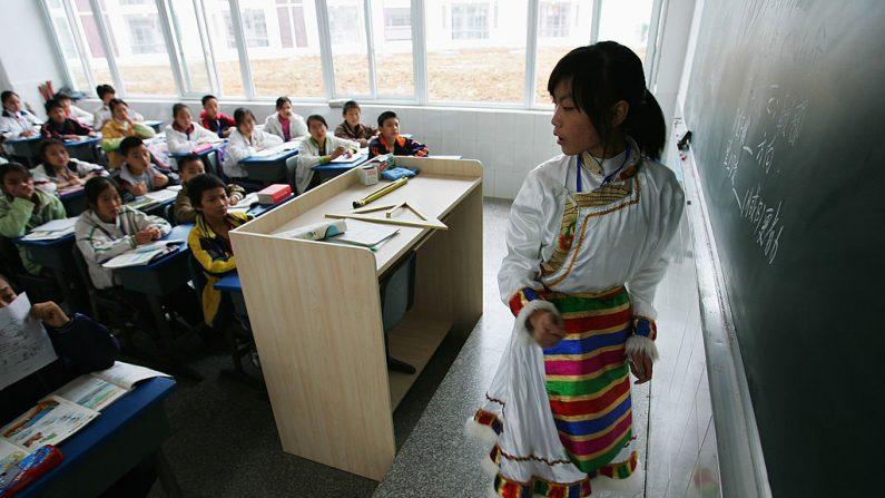 """Imagen de archivo de una alumna tibetana de las regiones montañosas que estudia en una escuela experimental el 7 de noviembre de 2007 en Chengdu, capital de la provincia de Sichuan en el suroeste de China. Los estudiantes que asisten a la escuela reciben apoyo financiero del proyecto """"Fénix Dorado"""", por el cual el gobierno local paga todas las tarifas y gastos de manutención. (Foto de Guang Niu/Getty Images)"""