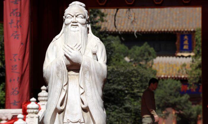 Un hombre camina junto a una estatua de Confucio en el Templo de Confucio en Beijing el 28 de septiembre de 2010. (LIU JIN/AFP vía Getty Images)