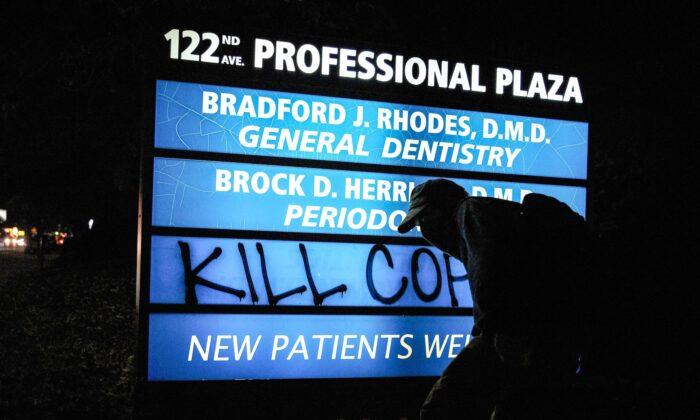 """Un individuo enmascarado pinta las palabras """"Maten a los policías"""" en un cartel comercial durante las protestas en Portland, Oregon, el 5 de septiembre de 2020. (Allison Dinner/AFP vía Getty Images)"""