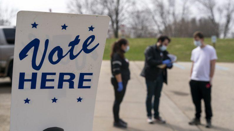 Los trabajadores electorales durante la votación en la acera en Madison, Wisconsin, el 7 de abril de 2020. (Andy Manis/Getty Images)