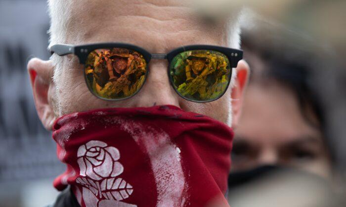 Un militante se ve reflejado en las gafas de un manifestante de Antifa durante una manifestación y contramanifestación en Stone Mountain, Ga., el 15 de agosto de 2020. (Logan Cyrus/AFP vía Getty Images)