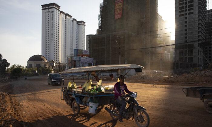 Una motocicleta con remolque avanza por un camino de tierra en Sihanoukville, Camboya, el 16 de febrero de 2020. (Paula Bronstein/Getty Images)