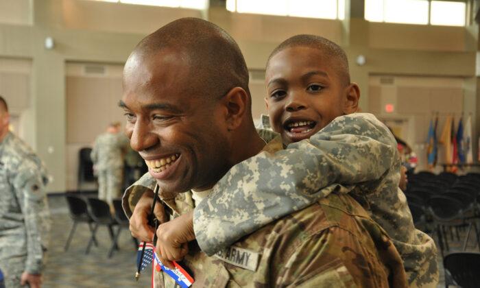 El Capitán de la Guardia Nacional del Ejército de Georgia, Chad Tyson, recibe un abrazo de su hijo Chase durante la ceremonia de bienvenida a su hogar en Marietta, Georgia, después de un despliegue de 10 meses en Afganistán, el 22 de noviembre de 2013. (Cortesía de la página de Flickr de la Guardia Nacional)