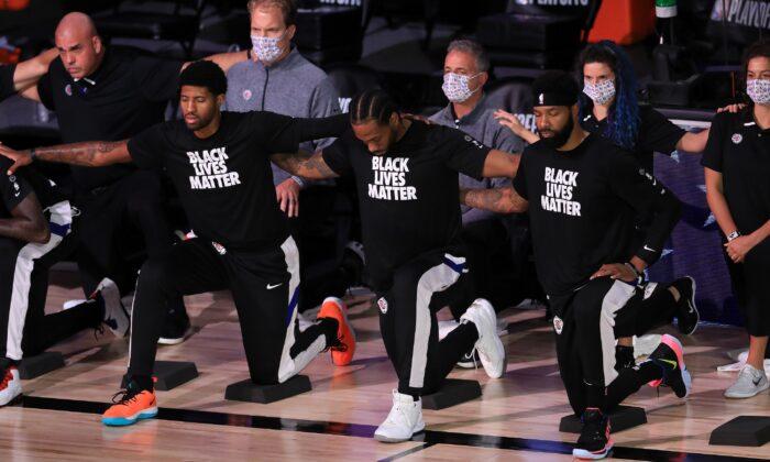 Los jugadores y el personal de Los Angeles Clippers se arrodillan durante el himno nacional antes de su partido contra los Denver Nuggets en el Complejo Deportivo ESPN Wide World Of Sports en Lake Buena Vista, Florida, el 11 de septiembre de 2020. (Michael Reaves/Getty Images)