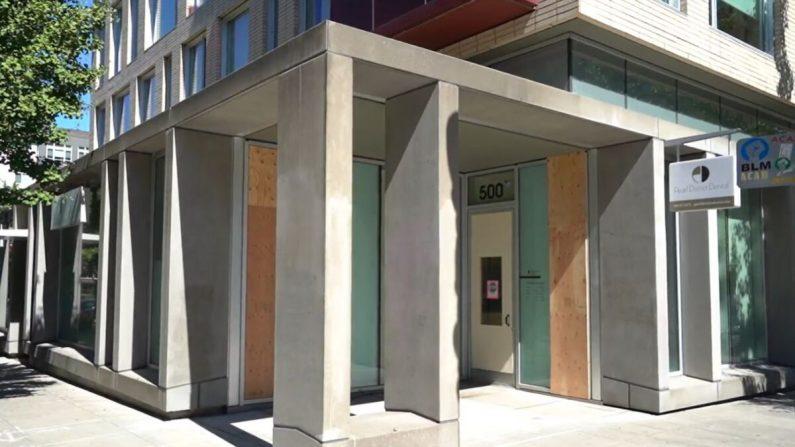 Tablas de madera cubren los paneles de vidrio destruidos recientemente por los disturbios, en el Pearl District Dental, en Portland, Ore., el 2 de septiembre de 2020. (Roman Balmakov/The Epoch Times)