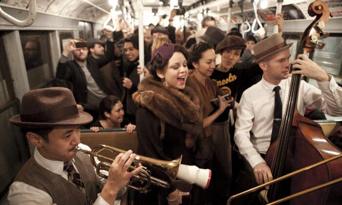 Pasajeros llevan ropa de épocas pasadas en los vagones del metro de Nueva York el 8 de diciembre de 2013. (Samira Bouaou/Epoch Times)