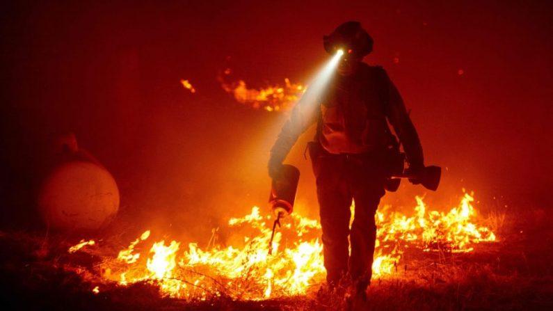 Los bomberos cortaron las líneas defensivas y encendieron fuegos para proteger varios edificios detrás de una estación de bomberos de CalFire durante el incendio de Bear, que forma parte de los incendios del North Lightning Complex en el área de Berry Creek del condado no incorporado de Butte, California, el 9 de septiembre de 2020. (Josh Edelson/AFP vía Getty Images)