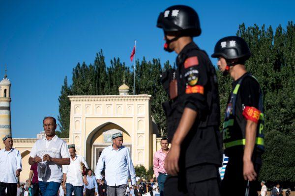 La policía vigila mientras los musulmanes abandonan la mezquita de Id Kah después de la oración de la mañana en Eid al-Fitr, Kashgar (Xinjiang), el 26 de junio de 2017. (Johannes Eisele/AFP/Getty Images)