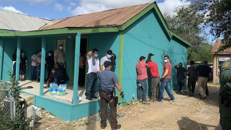 Fotografía cedida el Servicio de Control de Inmigración y Aduanas (ICE) donde se ve a varios agentes mientras arrestan a unos 32 inmigrantes indocumentados que estaban escondidos en una casa de seguridad en Laredo, Texas. EFE/ICE