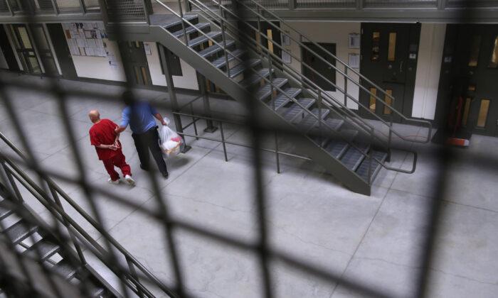 Un guardia escolta a un detenido a la población general en el centro de detención de Adelanto, en Adelanto, California, el 15 de noviembre de 2013. (John Moore/Getty Images)