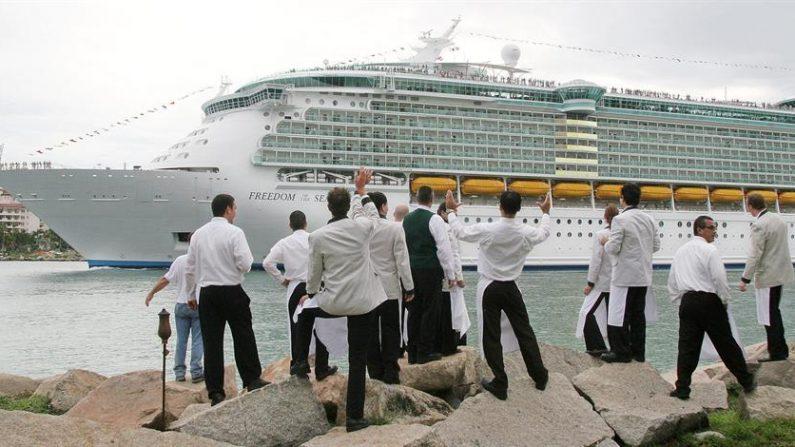 """Un grupo de camareros observa la partida del crucero """"Freedom of the Seas"""", el más grande del mundo, que atracó por breves horas en el puerto de Miami, Florida (EEUU). EFE/John Riley/Archivo"""