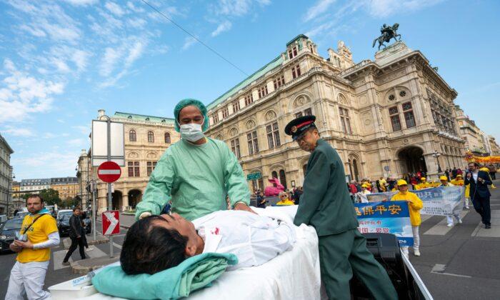 Los practicantes de Falun Gong en Viena, Austria, realizan una demostración de sustracción de órganos a practicantes encarcelados en China, durante una protesta contra la importación de órganos humanos de China a Austria, el 1 de octubre de 2018. (JOE KLAMAR/AFP a través de Getty Images)