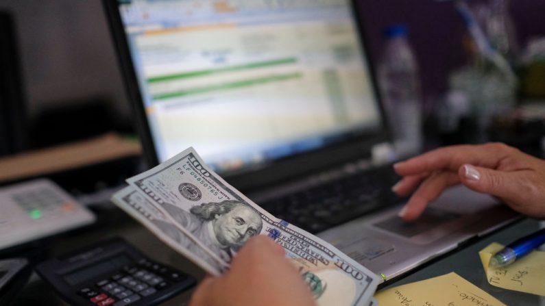 Una pequeña empresaria cuenta y paga sus artículos de papelería de oficina en dólares americanos el 26 de junio de 2019 en Caracas, Venezuela. (Foto de Matias Delacroix/Getty Images)