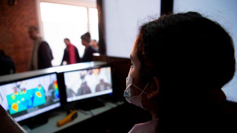 Una funcionaria del aeropuerto, con una máscara facial, comprueba la pantalla de un escáner térmico. (Foto de PRAKASH MATHEMA/AFP vía Getty Images)