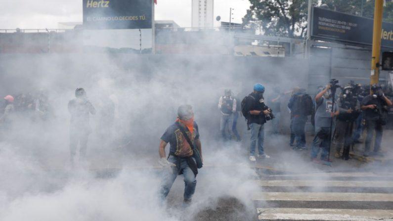 Un manifestante anti-Maduro camina cubriéndose la cara con el gas lacrimógeno lanzado por la Policía Nacional de Venezuela durante una manifestación contra el régimen de Nicolás Maduro el 10 de marzo de 2020 en Caracas, Venezuela. (Leonardo Fernández Viloria/Getty Images)
