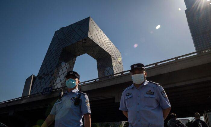 Agentes de policía con máscaras caminan mientras se ve el edificio de la sede de la Televisión Central de China (CCTV) (izq, atrás), en Beijing, el 19 de mayo de 2020. (Nicolas Asfouri/AFP a través de Getty Images).