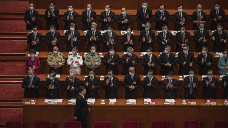 El líder chino Xi Jinping (abajo) llega a la sesión de clausura de la conferencia legislativa títere del régimen chino mientras otros funcionarios del Partido Comunista aplauden, en Beijing, el 28 de mayo de 2020. (Kevin Frayer/Getty Images)