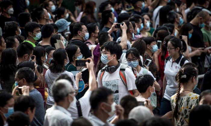 """Estudiantes caminan fuera de una escuela después de terminar el Examen Nacional de Ingreso a la Universidad, conocido como """"gaokao"""", fuera de una escuela en Wuhan en la provincia de Hubei en China central el 8 de julio de 2020. (STR/AFP vía Getty Images)"""