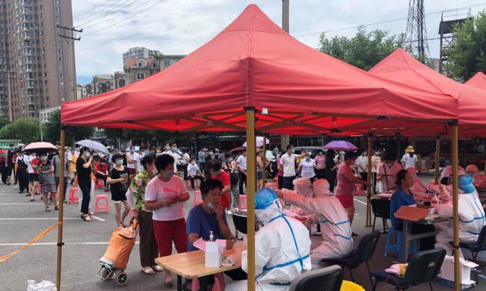 Personas hacen cola para hacerse los test de COVID-19 en un improvisado centro de pruebas en Dalian, en la provincia de Liaoning, al noreste de China, el 26 de julio de 2020. (STR/AFP vía Getty Images)