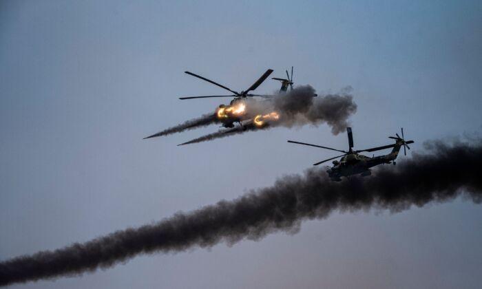 """Helicópteros lanzan misiles durante los ejercicios militares """"Cáucaso-2020"""" que reúnen a tropas de China, Irán, Pakistán y Myanmar, junto con la exsoviética Armenia, Azerbaiyán y Bielorrusia en el rango de Kapustin Yar en la región de Astracán, sur de Rusia el 25 de septiembre de 2020. (DIMITAR DILKOFF/AFP a través de Getty Images)"""