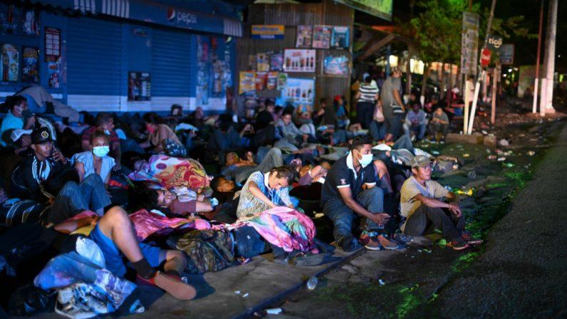 Migrantes hondureños, parte de una caravana que se dirige a los Estados Unidos, descansan en una acera en Entre Ríos, Guatemala, después de haber cruzado la frontera de Honduras el 1 de octubre de 2020. (Foto de JOHAN ORDONEZ/AFP vía Getty Images)