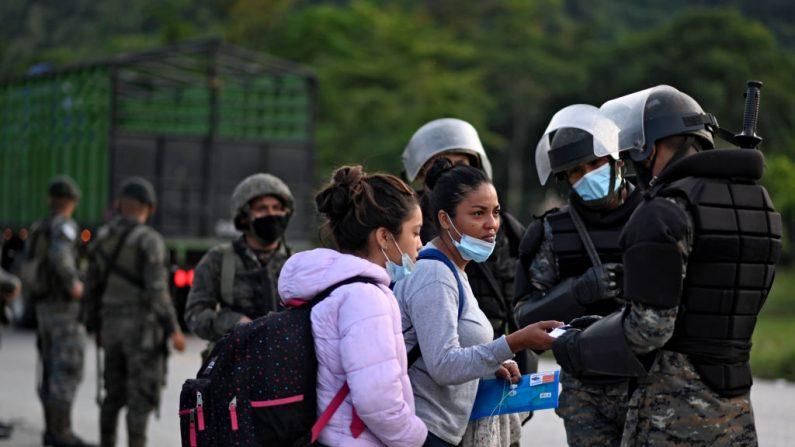 Migrantes hondureños, parte de una caravana con destino a Estados Unidos, son interceptados por miembros del ejército guatemalteco que les piden documentos en San Luis, departamento de Petén, Guatemala, el 3 de octubre de 2020. (Foto de JOHAN ORDONEZ/AFP vía Getty Images)