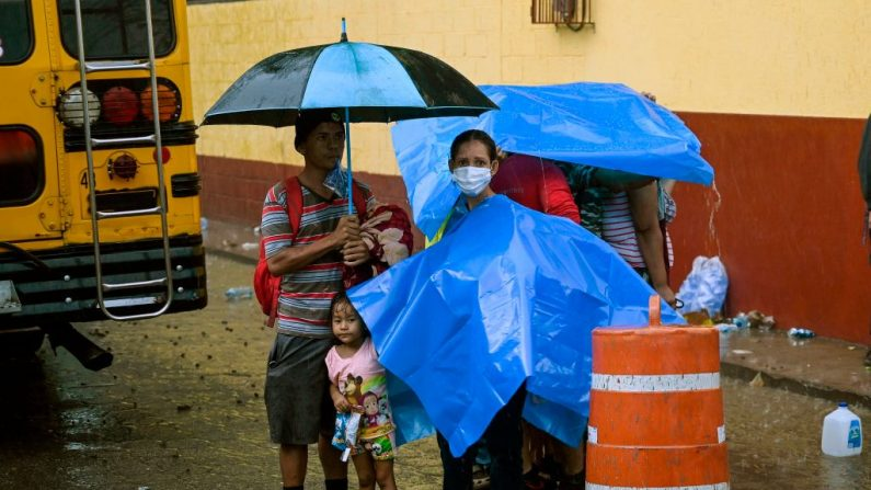 Migrantes hondureños, parte de una caravana de migrantes con destino a los Estados Unidos, se refugian de la lluvia en el exterior de un refugio para migrantes en el municipio de San Marcos (Guatemala), el 3 de octubre de 2020. (Foto de ALFREDO ESTRELLA/AFP vía Getty Images)