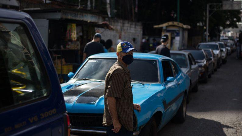 Un hombre espera junto a su coche en una fila para repostar el tanque de su vehículo cerca de una gasolinera en Caracas (Venezuela) el 5 de octubre de 2020. (Foto de CRISTIAN HERNANDEZ/AFP vía Getty Images)