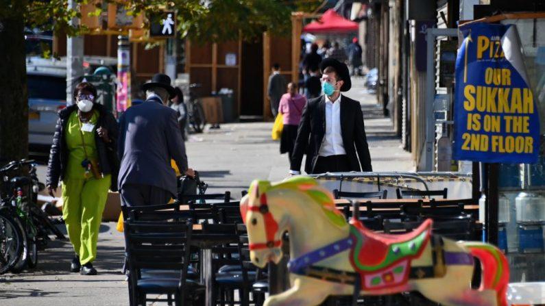 La gente pasa por delante de las tiendas cerradas en la sección de Borough Park de Brooklyn, uno de los cinco distritos de la ciudad de Nueva York, el 9 de octubre de 2020. (Foto de ANGELA WEISS/AFP vía Getty Images)