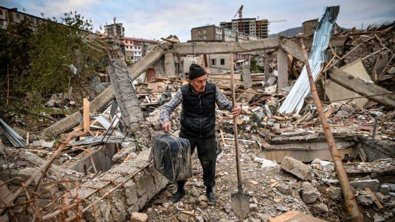 El oficial de policía retirado Genadiy Avanesyan, de 73 años, busca sus pertenencias en los restos de su casa, que se dice fue destruida por el bombardeo azerí, en la ciudad de Stepanakert el 10 de octubre de 2020. (Foto de ARIS MESSINIS/AFP vía Getty Images)