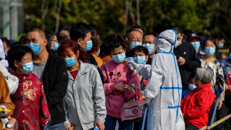 Un profesional sanitario controla la temperatura de varios residentes mientras se alinean para hacerse el test de COVID-19 en Qingdao (provincia de Shandong), en el este de China, el 12 de octubre de 2020. (STR/AFP a través de Getty Images)