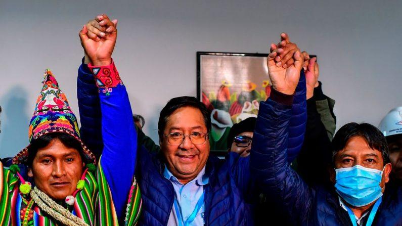 El candidato presidencial del partido Movimiento al Socialismo de Bolivia, Luis Arce (d), celebra con su compañero de fórmula David Choquehuanca (d) la madrugada del 19 de octubre de 2020 en La Paz, Bolivia. (Foto de RONALDO SCHEMIDT/AFP vía Getty Images)