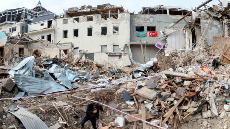 Un hombre camina entre los escombros de los edificios destruidos por los bombardeos durante el conflicto militar en curso entre Armenia y Azerbaiyán por la región separatista de Nagorno-Karabaj, en una zona residencial de la ciudad de Ganja, Azerbaiyán, el 22 de octubre de 2020. (TOFIK BABAYEV/AFP vía Getty Images)