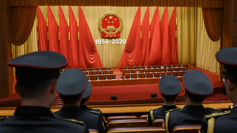 Miembros de la banda del Ejército de Liberación Popular observan cómo el líder chino, Xi Jinping, miembros de nivel medio y superior, asisten a una ceremonia que marca el 70 aniversario de la participación de China en la Guerra de Corea, el 23 de octubre de 2020 en el Gran Salón del Pueblo en Beijing, China. (Kevin Frayer/Getty Images)