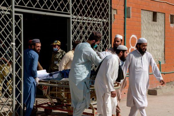 Hombres empujan una camilla que lleva a una víctima herida en la explosión de una bomba en una escuela religiosa, en un hospital de Peshawar (Pakistán) el 27 de octubre de 2020. (Foto de ABDUL MAJEED/AFP vía Getty Images)